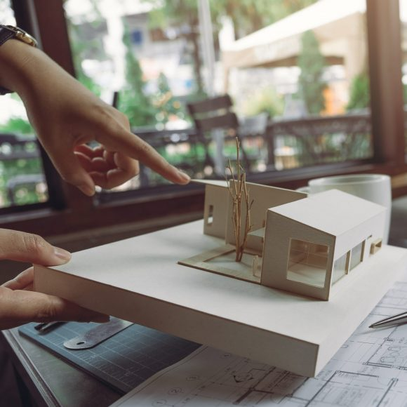 The colleague team of architects discussing and pointing at architecture model with shop drawing paper and laptop on table